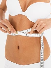 Young Woman Measuring Waist --- Image by © moodboard/Corbis